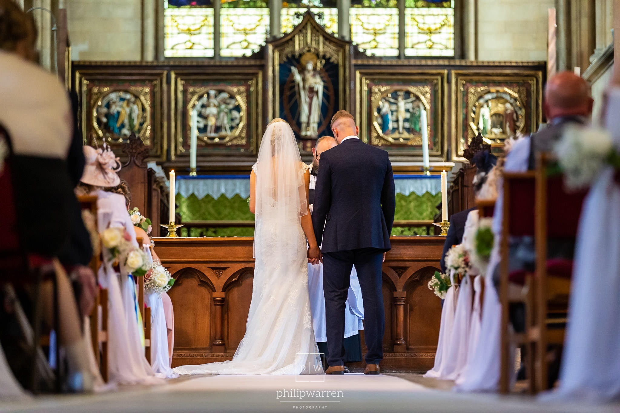 photo taken from at the back of the church lookign down the aisle at the bride and groom holding hands during the ceremony at st marys church in chepstow