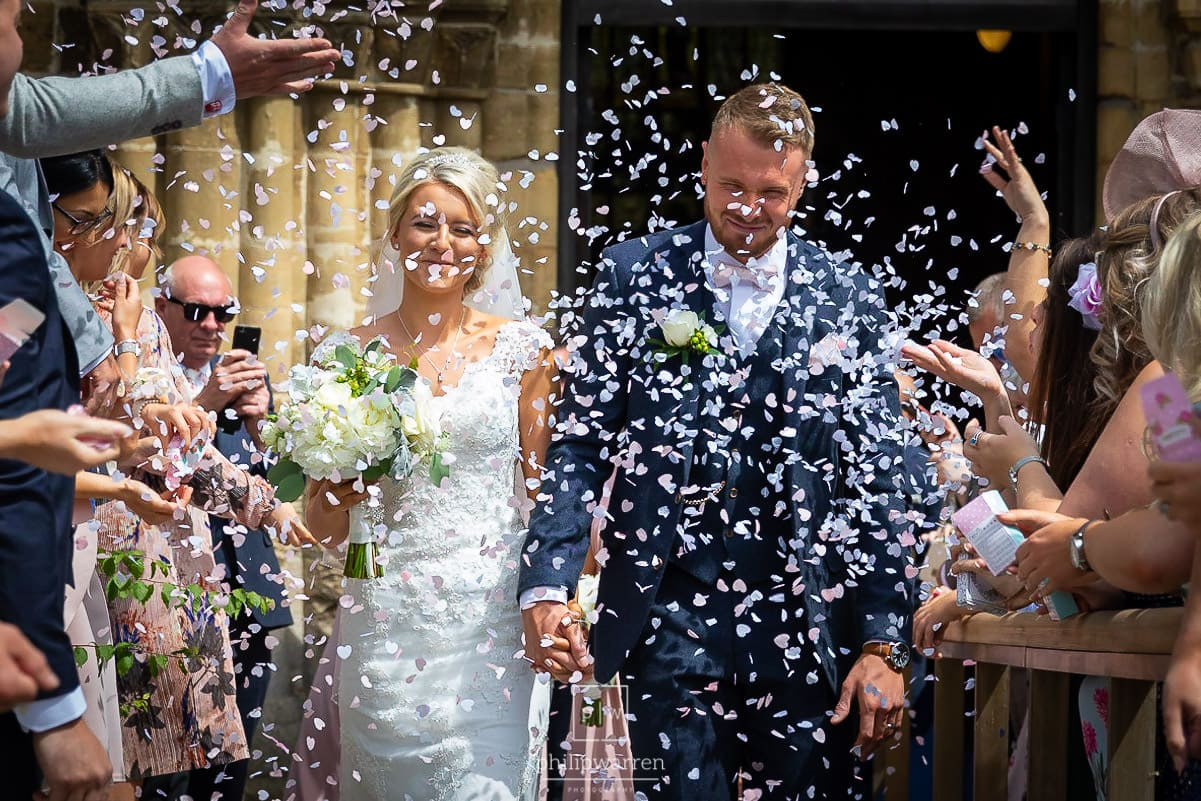 bride and groom getting covered in confetti outside of the church in cheopstow as they walk up the pathway from the church holding hands before st tewdrics house